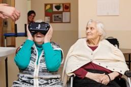 Laimės dienos akimirka - dvi senolės žiūrinčios su virtualios realybės akiniais
