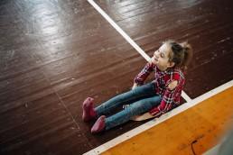Mergaitė sėdi ant žemės šiuolaikinio cirko dirbtuvių metu